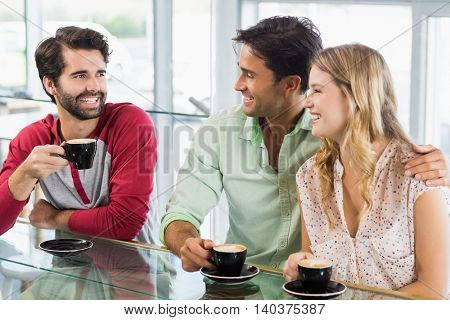 Smiling woman and two men having cup of coffee in cafe