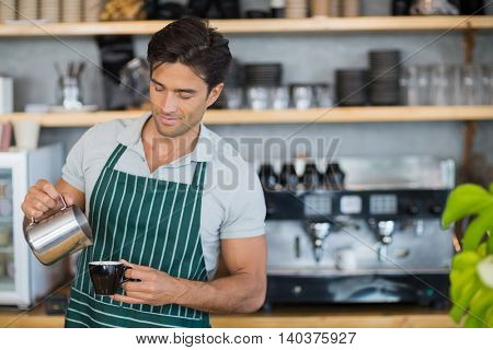 Smiling waiter pouring a cup of coffee in cafe