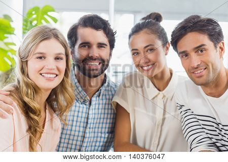 Portrait of smiling friends sitting together in cafe