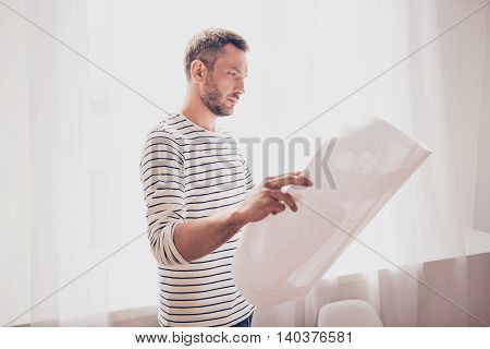 Concentrated Architect Holding Blueprint And Looking At Scheme Of His Project
