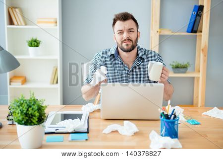 Sick Businessman With Grippe Sitting In Office And Holding A Cup Of Tea