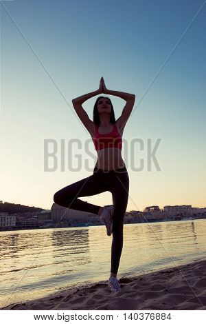 Portrait Of Young Healthy Woman Practising Yoga On Sunset