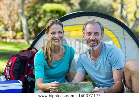 Portrait of hiker couple holding map in forest