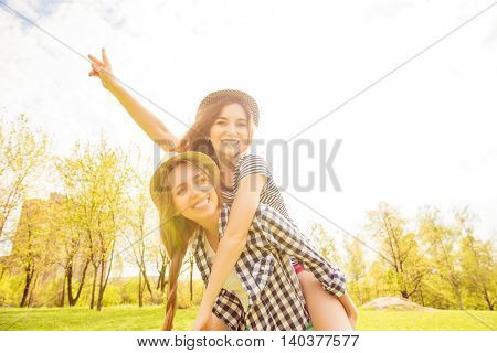 Portrait Of Cheerful Girl Having Fun And Piggybacking Her Sister