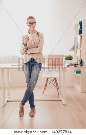 Happy Businesswoman Standing Near Her Working Place And Drinking Coffee