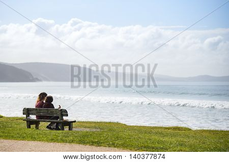 couple people on wooden bench near beautiful beach landscape look out to sea in summer of Lorne (a town on Great Ocean Road route) Victoria Australia