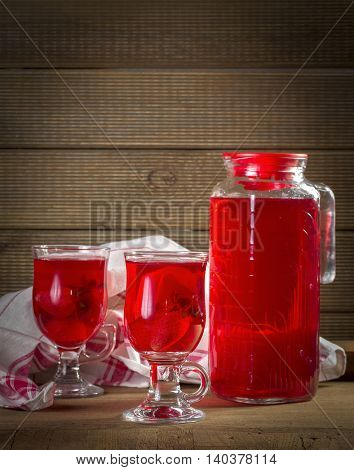 Jug and glasses with strawberry juice on vintage background