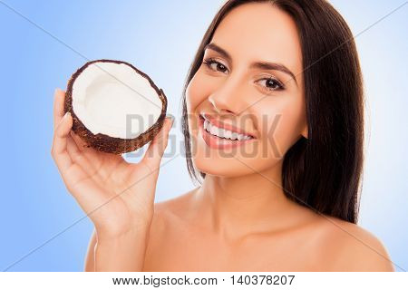 Portrait Of Young Woman With Beaming Smile Holding Half Of Coconut In Hand