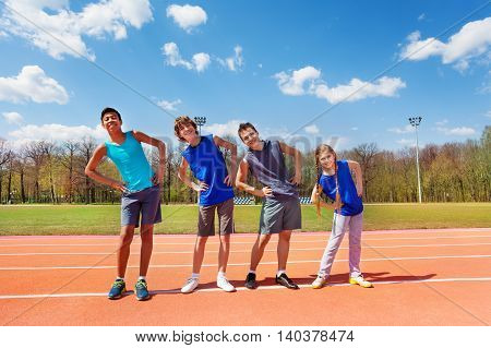 Four happy teenagers doing side bending exercises standing in a row according to height outside on the track
