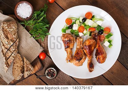 Appetizing Oven Baked Golden Chicken Drumsticks And Greek Salad. Top View
