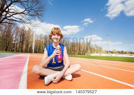 Happy teenage sportsman having rest after working out, drinking water sitting on track in the stadium