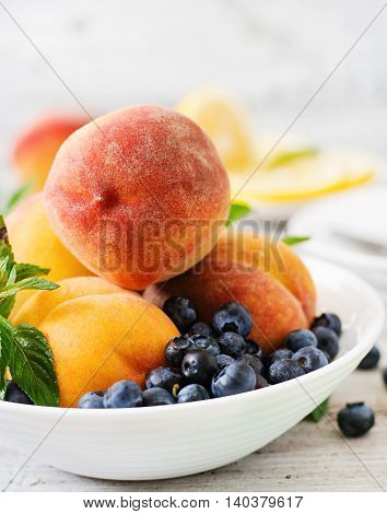 Fresh Peaches And Blueberries In Bowl On A Light Wooden Background In Rustic Style