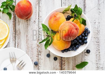 Fresh Peaches And Blueberries In Bowl On A Light Wooden Background In Rustic Style. Top View