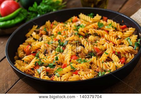 Vegetarian Vegetable Pasta Fusilli With Zucchini, Mushrooms And Capers In Pan On Wooden Table.