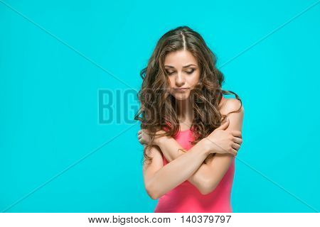 The young woman's portrait with thoughtful emotions on blue background