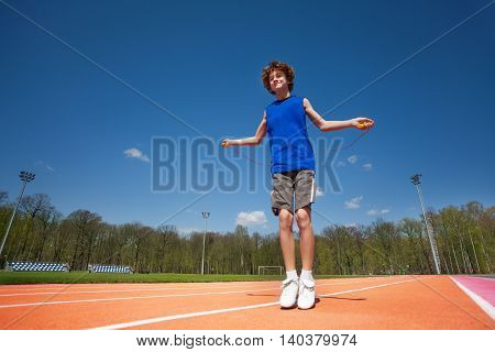 Bottom view of smiling teenage boy jumping the rope outside on the stadium on sunny spring day