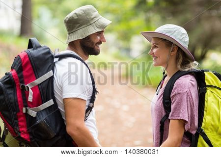 Hiker couple looking at each other in forest at countryside