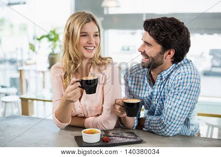Happy couple having cup of coffee in cafe