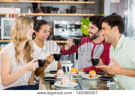 Group of friends having cup of coffee together in cafe