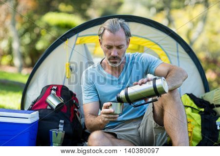 Hiker pouring water from thermos bottle in forest