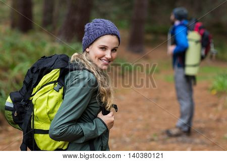 Beautiful woman looking back while hiking in forest at countryside
