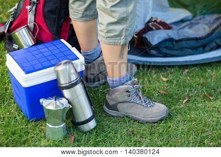 Female hikers feet with picnic essentials in forest