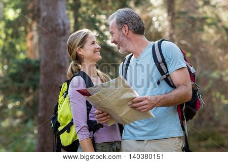 Happy hiker couple holding map and looking at each other