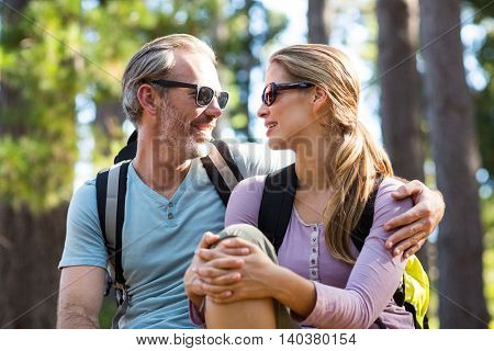 Smiling couple looking face to face while relaxing in forest
