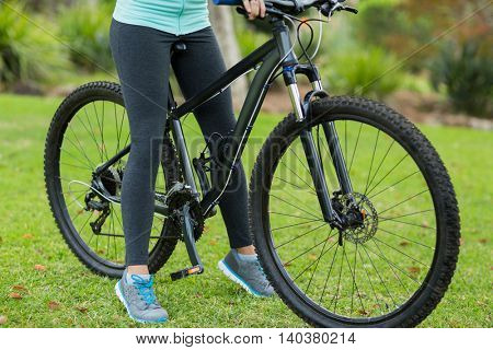 Low section of female cyclist in forest