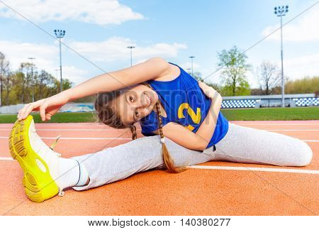 Happy teenage girl in sportswear making yoga stretching on the stadium on sunny day