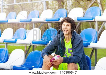 Happy smiling teenage athlete having rest after workout, sitting at the tribune