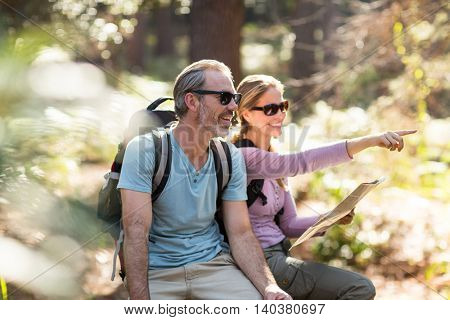 Hiker couple with map pointing in the distance at forest