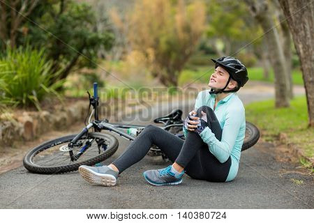 Female cyclist in pain holding her injured leg at countryside