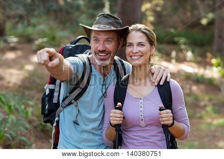 Hiker couple pointing at distance in forest