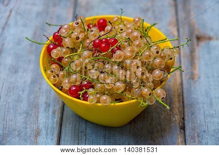Red currants and white currnts in yellow bowl on the rustic table