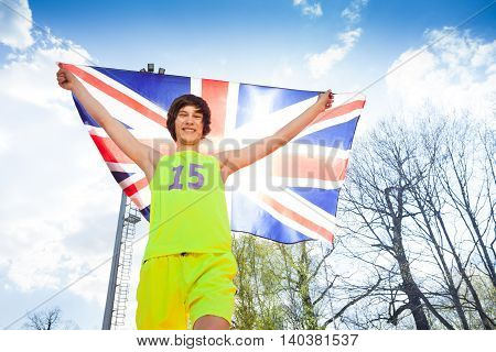 Bottom view of happy young athlete, teenage runner holding flag of Great Britain against blue sky on the stadium
