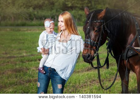 Mother and daughter standing near a horse. Mom looks into the distance