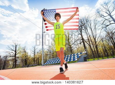 Full-length portrait of teenage boy in sportswear, running with American flag outside on the track