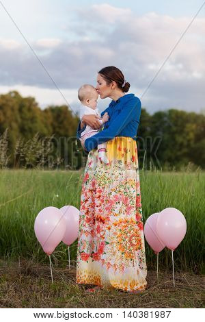 Mom and daughter on the field among the balloons. Mother kissing daughter