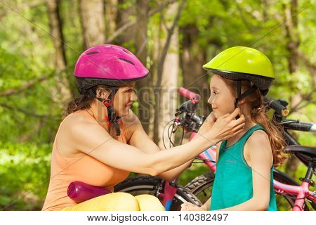 Sporty mother helping her young daughter to clasp bicycle helmet before cycling