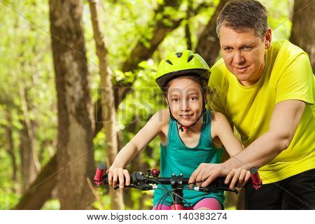 Portrait of cute happy girl in bicycle helmet learning to cycle with her father in the park