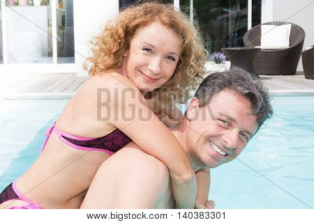 Happy and lovely middle aged couple at swimming pool