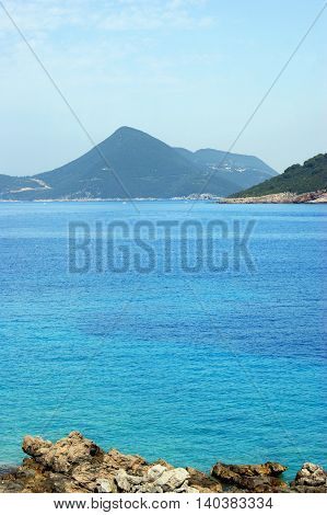 Bright blue transparent waters of the sea and mountains in the background