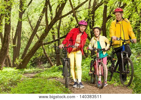 Teenage girl with parents walking on mounting biking trail in spring sunny woodland and holding bikes