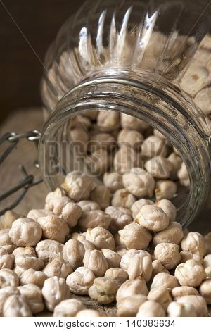 Spilled chickpeas from a glass jar on a wooden background