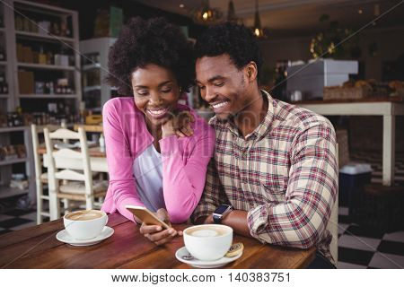 Happy young couple sitting at table using mobile phone in cafeteria