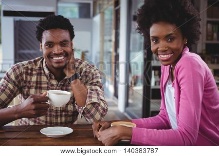 Portrait of happy young couple having coffee in cafeteria