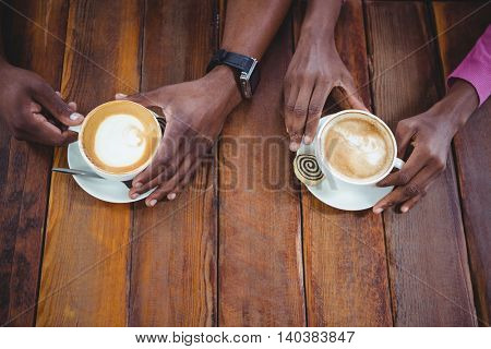 Couple hand holding cup of coffee in cafeteria