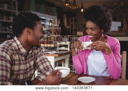 Young couple interacting with each other while having coffee in cafeteria