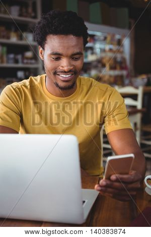 Young man text messaging on mobile phone while using laptop in cafeteria